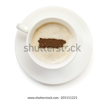 A cup of coffee with foam and powder in the shape of Puerto Rico.(series) - stock photo