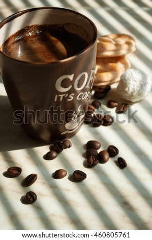 A cup of coffee with froth and coffee beans and sweets on the table