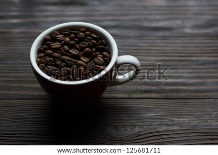 A cup of coffee with grains on the background of the wooden sill