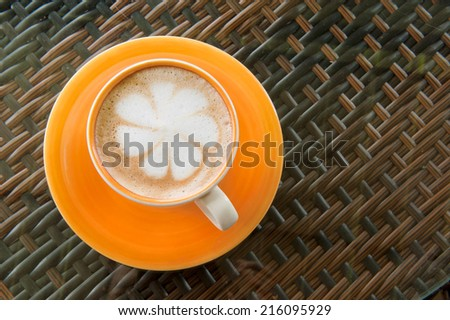 A cup of coffee with heart pattern in a orange cup on wooden background - stock photo