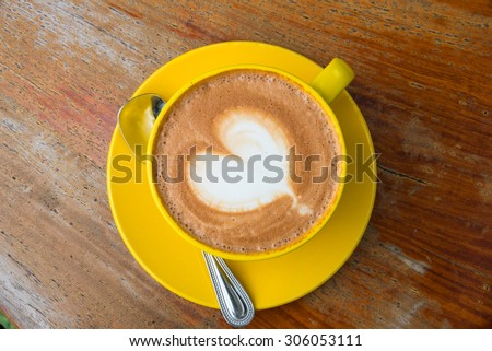 A cup of coffee with heart pattern in a yellow cup on wooden background - stock photo