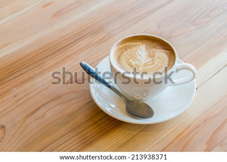 A cup of coffee with leaf pattern in a white cup on wooden background - stock photo