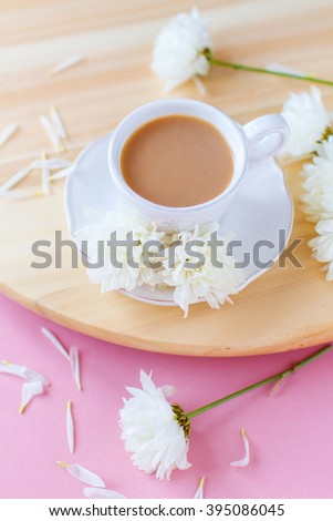 A cup of coffee with milk on a wooden board , spring flowers on a pink background - stock photo