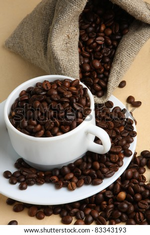 A cup of coffee with sack of coffee beans.