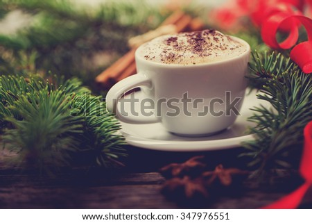 A cup of coffee with the branches of the Christmas tree on a wooden table - stock photo