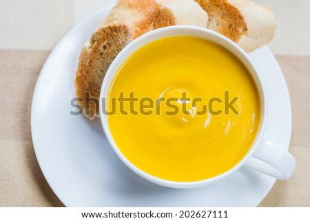 A cup of creamy pumpkin soup with lightly toasted baguette slices
