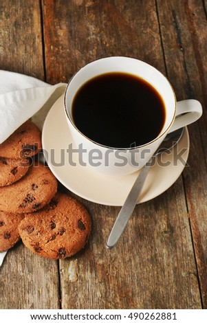 a cup of dark coffee, with baked chocolate chips cookies