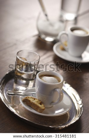 A cup of espresso macchiato with cantuccini and a glass of water - stock photo