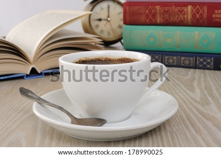 A cup of fragrant black coffee on the table against the background of an open book