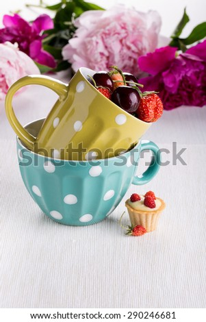 A cup of fresh berries and mini tartlet with custard and wild strawberry. - stock photo