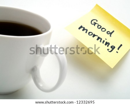 A cup of fresh coffee and a yellow note with this text: 'Good morning!' - stock photo