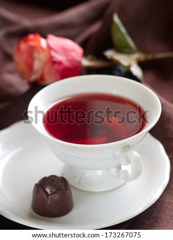 A cup of fruit tea with chocolate candy, selective focus