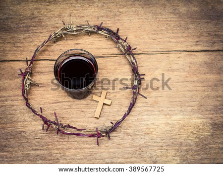 a cup of grape juice with wooden cross and  metal Barbed Wire made like the crown of thorns of Jesus on wooden background, Christian concept, Easter background with copy space - stock photo