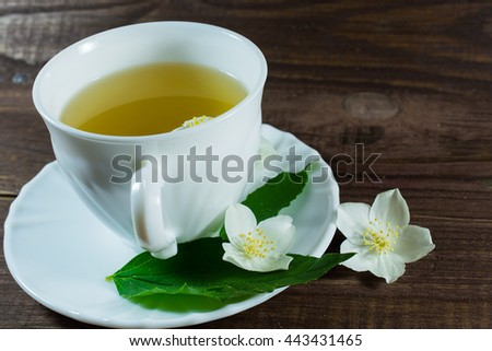 A cup of green jasmine tea with white jasmine flowers and green leafs on a wooden background. front view - stock photo