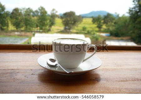 A cup of green tea in a white cup with teaspoon on wooden table.