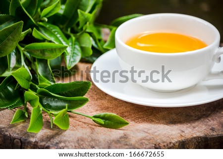 a cup of green tea on wood board, drink for health