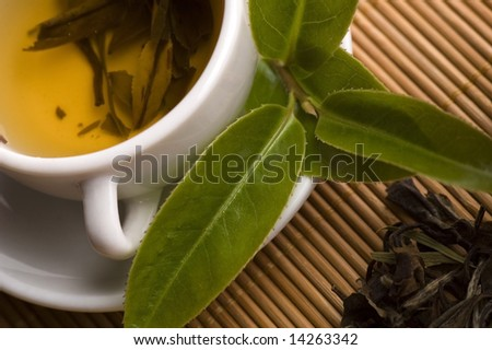 a cup of green tea with freh leaves on the bamboo tray - stock photo