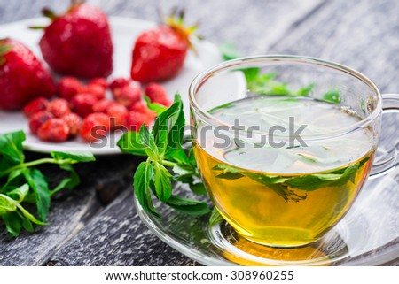 A cup of herbal tea with fresh mint and ripe strawberry on wooden background - stock photo