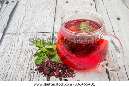 A cup of hibiscus tea and fresh mint leaves on wooden background
