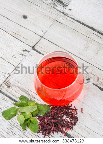 A cup of hibiscus tea and mint leaves over wooden background