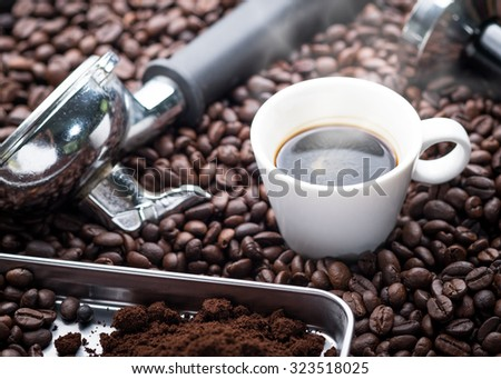 A cup of hot and fresh espresso coffee lay on many roast coffee beans also see an espresso machine group head. - stock photo
