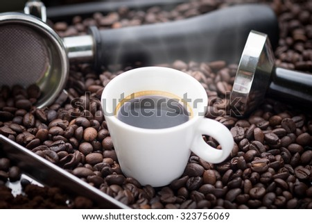 A cup of hot and fresh espresso coffee lay on many roast coffee beans also see an espresso machine group head, coffee tamper and ground coffee lay on many roasted coffee beans. - stock photo