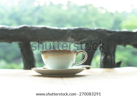 A cup of hot coffee and blurry green leaf in nature