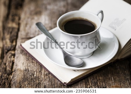 A cup of hot coffee and book. Romantic background with retro filter effect - stock photo