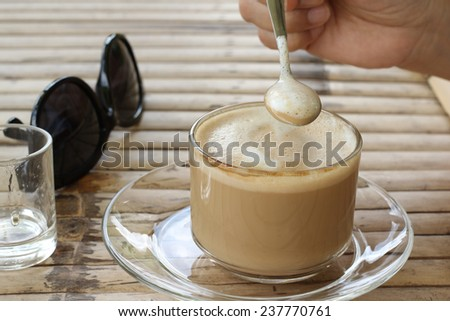 A cup of hot coffee on bamboo table - stock photo