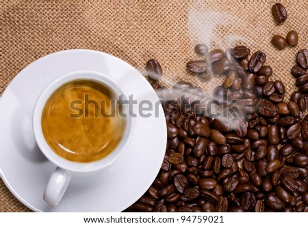 a cup of hot coffee sacking with coffee beans - stock photo