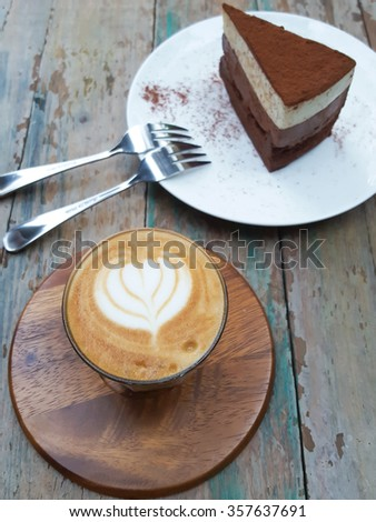 A Cup of hot latte art coffee and delicious chocolate cake on wooden table - stock photo