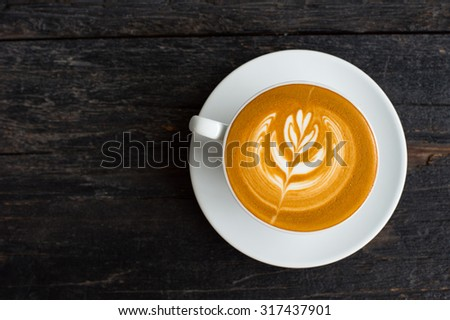 A Cup of hot latte art coffee on wooden table  - stock photo
