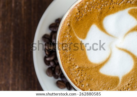 A Cup of hot latte art coffee on wooden table, Close-up - stock photo