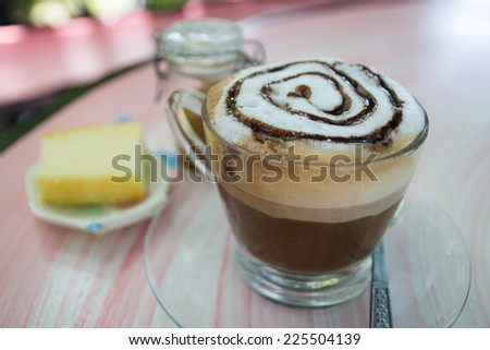 a cup of hot mocha topping with foamy milk and chocolate sauce - stock photo