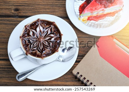 a cup of latte art hot coffee with notebook paper and crape cake on wood table. - stock photo
