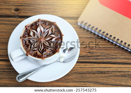a cup of latte art hot coffee with notebook paper on wood table. - stock photo
