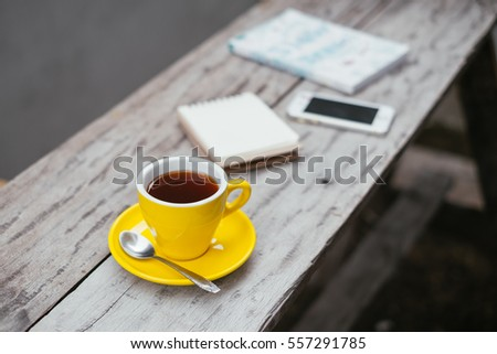 A cup of lemon tea and notepad, book, mobile on wooden table, selective focus.
