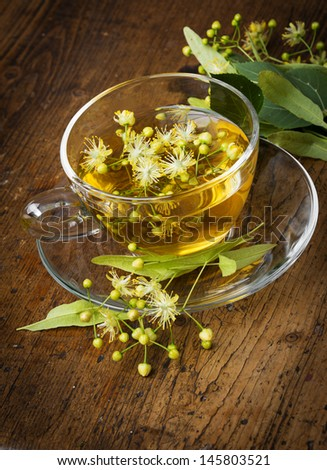 a cup of linden tea on an old wooden table - stock photo