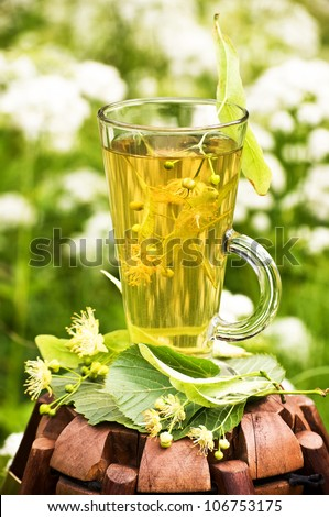 A cup of linden tea with linden flowers outdoors