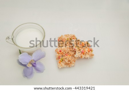 A cup of milk and whole gain cereal with vast of flowers by whiten background - stock photo