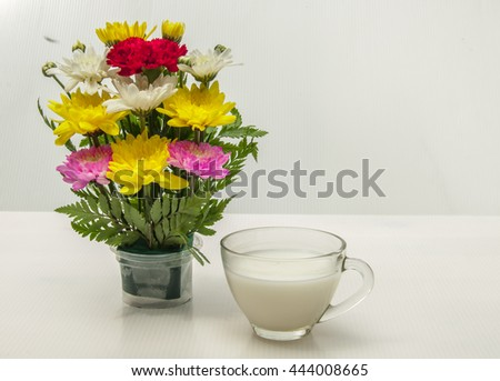 A cup of milk with vast of flowers by whiten background - stock photo