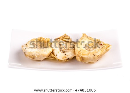 a cup of Preserved Artichokes hearts with herbs isolated ovaer a white background