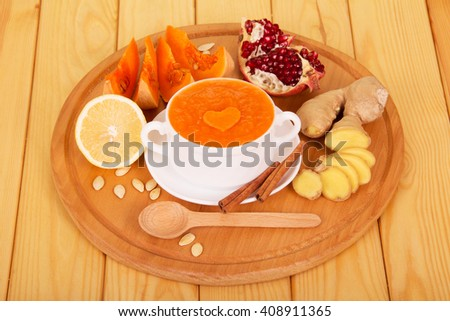 A cup of pumpkin puree, ginger, lemon and garnet on a background of light wood. - stock photo