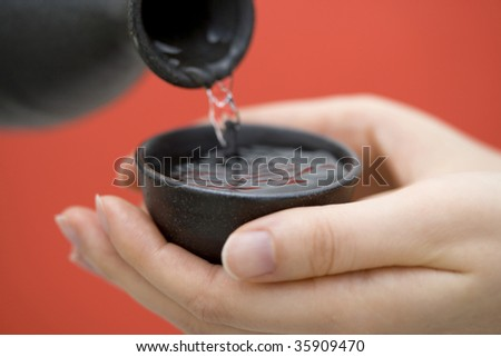 A cup of sake pouring from its bottle - stock photo