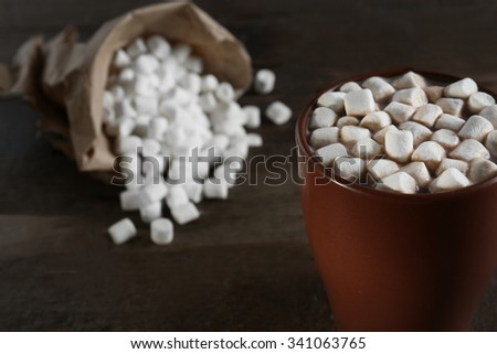 A cup of tasty cocoa and marshmallow on wooden table - stock photo
