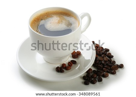 A cup of tasty drink and scattered coffee grains, isolated on white - stock photo