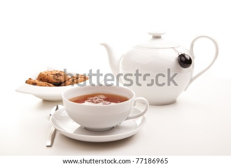 A cup of tea, a teapot and cookies