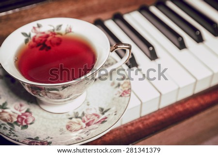 A cup of tea and a piano in a vintage toning - stock photo