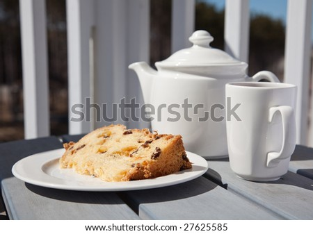 A cup of tea and a slice of fruit cake served on a balcony - stock photo