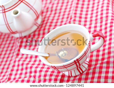 A cup of tea and a teapot on a red checked cloth - stock photo